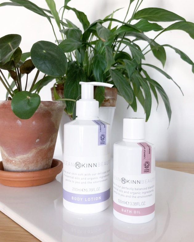 Two white bottles sit on a white tile in front of two green plants. The bottles are of body lotion and bath oil.