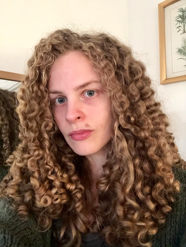 a white woman with long curly hair wearing a green cardigan